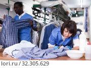 Купить «Woman dry cleaning clothes in laundry», фото № 32305629, снято 15 января 2019 г. (c) Яков Филимонов / Фотобанк Лори