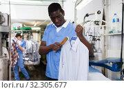 Купить «Laundry worker during daily work», фото № 32305677, снято 15 января 2019 г. (c) Яков Филимонов / Фотобанк Лори