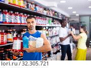 Купить «Young man with sports nutritional supplements», фото № 32305721, снято 22 января 2020 г. (c) Яков Филимонов / Фотобанк Лори