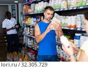 Купить «Man choosing food supplements in store», фото № 32305729, снято 7 апреля 2020 г. (c) Яков Филимонов / Фотобанк Лори