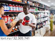 Купить «man choosing sports supplements and consulting African seller», фото № 32305741, снято 18 февраля 2020 г. (c) Яков Филимонов / Фотобанк Лори