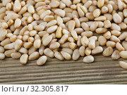 Купить «Picture of wooden desk with raw pine nut, nobody», фото № 32305817, снято 14 декабря 2019 г. (c) Яков Филимонов / Фотобанк Лори