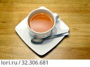 Белая чашка с облепиховым чаем стоит на блюдце. Стоковое фото, фотограф Ирина Борсученко / Фотобанк Лори