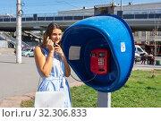Молодая симпатичная девушка разговаривает по таксофону на улице города. Стоковое фото, фотограф Иванов Алексей / Фотобанк Лори