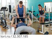 Купить «Sporty man and instructor practicing bench press», фото № 32307185, снято 5 ноября 2018 г. (c) Яков Филимонов / Фотобанк Лори