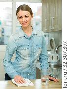 Купить «Positive housewife cleans the table in the kitchen», фото № 32307397, снято 12 ноября 2019 г. (c) Яков Филимонов / Фотобанк Лори