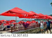 Купить «Budva, Montenegro - June 13.2019. City beach in the resort area with red umbrellas with Coca Cola brand», фото № 32307653, снято 13 июня 2019 г. (c) Володина Ольга / Фотобанк Лори