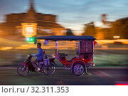 Купить «A Tuk Tuk Taxi in front of the Royal Palace at the Sisowath Quay at the Tonle Sap River in the city of Phnom Penh of Cambodia. Cambodia, Phnom Penh, November, 2017,», фото № 32311353, снято 30 марта 2020 г. (c) age Fotostock / Фотобанк Лори