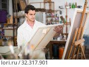 Купить «Male artist drawing in studio», фото № 32317901, снято 8 апреля 2017 г. (c) Яков Филимонов / Фотобанк Лори