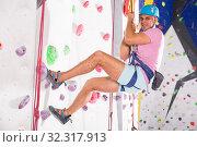 Купить «Male on climbing wall in special equipment», фото № 32317913, снято 9 июля 2018 г. (c) Яков Филимонов / Фотобанк Лори