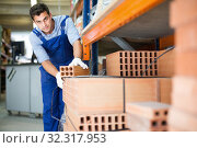Man assistant in uniform is calculating bricks. Стоковое фото, фотограф Яков Филимонов / Фотобанк Лори