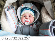Купить «Infant child dressed hat and warm suit with hood lying in stroller at winter walk, pacifier in mouth, looking at camera», фото № 32322257, снято 19 марта 2009 г. (c) Кекяляйнен Андрей / Фотобанк Лори