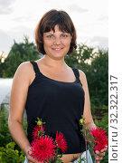 Pretty woman with red flowers, half length portrait, dressed black sleeveless top. Стоковое фото, фотограф Кекяляйнен Андрей / Фотобанк Лори
