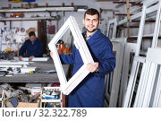 Купить «Production workers in coverall with different finished PVC profiles and windows at factory», фото № 32322789, снято 30 марта 2017 г. (c) Яков Филимонов / Фотобанк Лори