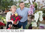 Купить «Man client is choosing blooming flower with help woman», фото № 32322869, снято 23 февраля 2018 г. (c) Яков Филимонов / Фотобанк Лори