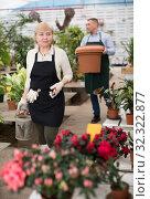 Купить «Portrait of female gardener with blooming flower who is taking care of them», фото № 32322877, снято 23 февраля 2018 г. (c) Яков Филимонов / Фотобанк Лори