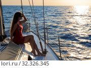 Купить «Молодая девушка сидит на яхте и всматривается вдаль на фоне заката», фото № 32326345, снято 7 августа 2015 г. (c) Игорь Долгов / Фотобанк Лори