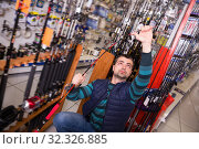 Positive fisherman looking new fishing rod. Стоковое фото, фотограф Яков Филимонов / Фотобанк Лори