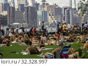 Millennials crowd Domino Park in the Williamsburg neighborhood in Brooklyn in New York to bake in the sun on Sunday, August 4, 2019. Редакционное фото, фотограф Richard Levine / age Fotostock / Фотобанк Лори