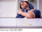Купить «Young man having problems with narcotics at home», фото № 32331881, снято 25 апреля 2019 г. (c) Elnur / Фотобанк Лори