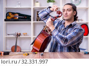 Купить «Young handsome repairman repairing cello», фото № 32331997, снято 4 апреля 2019 г. (c) Elnur / Фотобанк Лори