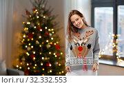 Купить «woman in christmas sweater with reindeer pattern», фото № 32332553, снято 9 декабря 2018 г. (c) Syda Productions / Фотобанк Лори