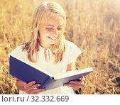 Купить «smiling young woman reading book on cereal field», фото № 32332669, снято 31 июля 2016 г. (c) Syda Productions / Фотобанк Лори