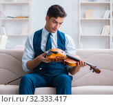 Купить «Young musician man practicing playing violin at home», фото № 32333417, снято 15 августа 2017 г. (c) Elnur / Фотобанк Лори
