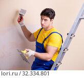 Купить «Young contractor employee applying plaster on wall», фото № 32334801, снято 15 марта 2018 г. (c) Elnur / Фотобанк Лори