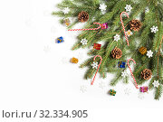 Купить «Decorated Christmas tree branch with cones, snowflakes and caramel canes on white background», фото № 32334905, снято 19 октября 2019 г. (c) Юлия Бабкина / Фотобанк Лори