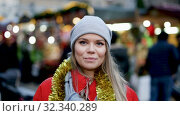 Купить «Portrait of smiling woman shopping on festive fair before Christmas», видеоролик № 32340289, снято 12 декабря 2018 г. (c) Яков Филимонов / Фотобанк Лори