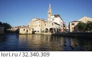 Купить «Catholic oratory of Madonna della Pesqueria and belfry of St. Andrew Cathedral on bank on Lemene river in Portogruaro, Veneto, Italy», видеоролик № 32340309, снято 18 ноября 2019 г. (c) Яков Филимонов / Фотобанк Лори
