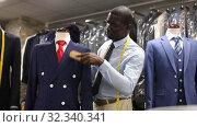 Seller is demonstrating jacket and tie in store. Стоковое видео, видеограф Яков Филимонов / Фотобанк Лори