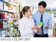 Woman pharmacist is recommending prescription medicine for korean man client in apothecary. Стоковое фото, фотограф Яков Филимонов / Фотобанк Лори
