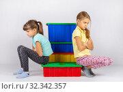 Две девочки поссорились, сидят на коробке и отвернулись друг от друга. Стоковое фото, фотограф Иванов Алексей / Фотобанк Лори