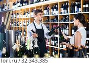 Купить «portrait of male seller showing bottle of wine to female customer in wine shop», фото № 32343385, снято 6 июня 2020 г. (c) Яков Филимонов / Фотобанк Лори