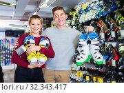 Woman and man are demonstrating their choice of ski boots. Стоковое фото, фотограф Яков Филимонов / Фотобанк Лори