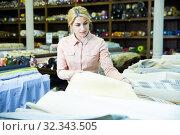 Купить «Woman looking for cloth in shop», фото № 32343505, снято 2 марта 2018 г. (c) Яков Филимонов / Фотобанк Лори