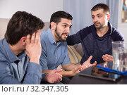Купить «Three anxious men discussing on sofa», фото № 32347305, снято 10 января 2018 г. (c) Яков Филимонов / Фотобанк Лори
