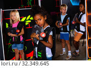 Cute little mulatto girl standing with laser pistol in dark lasertag room during game with friends. Стоковое фото, фотограф Яков Филимонов / Фотобанк Лори