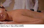 Купить «beautiful woman having hot stone massage at spa», видеоролик № 32352845, снято 19 октября 2019 г. (c) Syda Productions / Фотобанк Лори