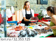 Polite female fishmonger standing behind counter of seafood store demonstrating raw bonito steak to woman buyer. Стоковое фото, фотограф Яков Филимонов / Фотобанк Лори