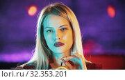 Купить «Gorgeous blonde young woman sitting by the bartender stand - drinking a beverage from the straw and looking in the camera - neon blue lighting», видеоролик № 32353201, снято 19 февраля 2020 г. (c) Константин Шишкин / Фотобанк Лори