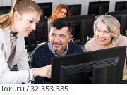 Купить «Business woman explaining something to coworkers, pointing at computer», фото № 32353385, снято 20 февраля 2019 г. (c) Яков Филимонов / Фотобанк Лори