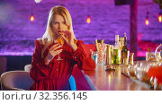 Gorgeous young woman sitting by the bartender stand - drinking a beverage from the straw. Стоковое фото, фотограф Константин Шишкин / Фотобанк Лори