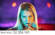 Gorgeous blonde young woman sitting by the bartender stand - drinking a beverage from the straw and looking in the camera - neon blue lighting. Стоковое фото, фотограф Константин Шишкин / Фотобанк Лори