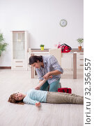Купить «Young couple in first aid concept at home», фото № 32356557, снято 10 мая 2019 г. (c) Elnur / Фотобанк Лори