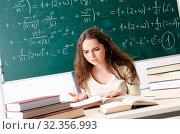 Купить «Young female math teacher in front of chalkboard», фото № 32356993, снято 2 ноября 2018 г. (c) Elnur / Фотобанк Лори