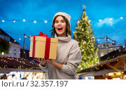 Купить «woman in hat holding gift box at christmas market», фото № 32357197, снято 30 сентября 2019 г. (c) Syda Productions / Фотобанк Лори