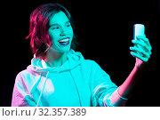 Купить «woman taking selfie by smartphone in neon lights», фото № 32357389, снято 30 сентября 2019 г. (c) Syda Productions / Фотобанк Лори